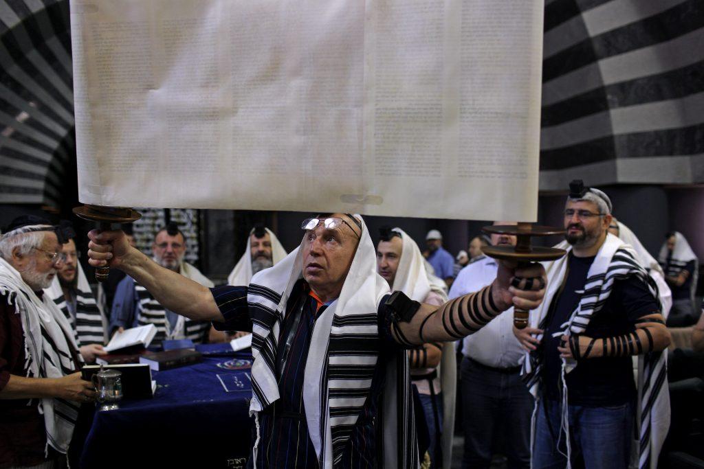 Un membre de la communauté juive expose la Torah avant de la ranger lors d'une prière matinale, dans le synagogue Golden Rose, à Dnipro, en Ukraine, le 8 septembre 2016.